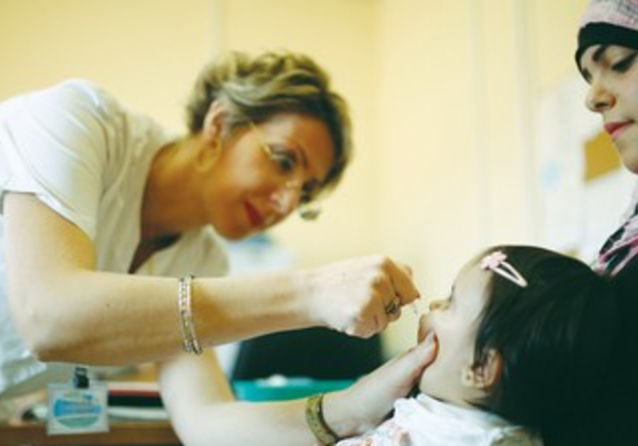 A MEDICAL staffer checks a girl