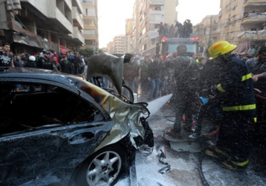 A firefighter extinguishes a fire on a car at the site of an explosion in Beirut.