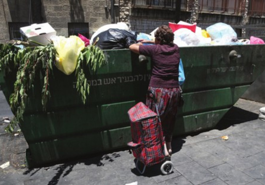A woman searches through a garbage container in central Jerusalem