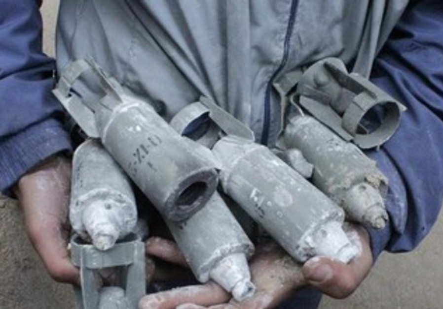 A Syrian boy holds unexploded cluster bombs in Aleppo.