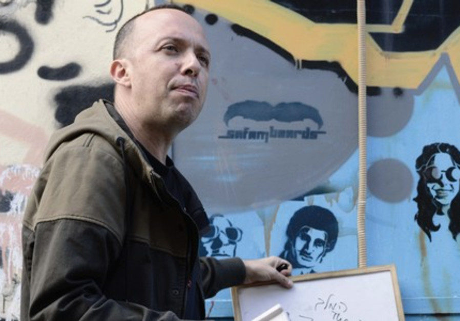 Guy Sharett points out a portrait of the late singer Zohar 'The King' Argov during tour of Florentin