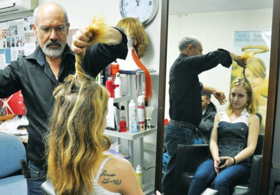 Model Katia Marshvin has her locks cut by Eli Ben-Zikri to use as a wig while undergoing treatment.