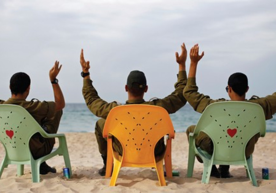 SOLDIERS TAKE a break on Zikim Beach, near Ashkelon. We're far more a 'sit back and relax' type of s