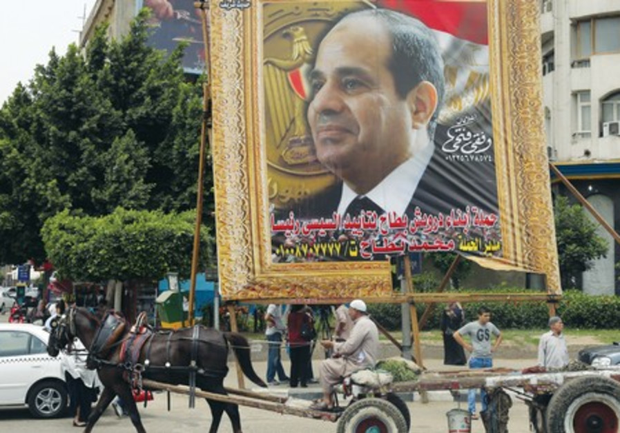 Man on a horse-drawn cart rides past banner depicting  Abdel Fattah al-Sisi in Cairo