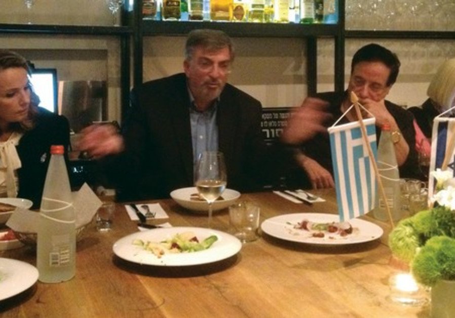 Greek Ambassador Spiros Lampridis (second from left) speaks to dinner attendees