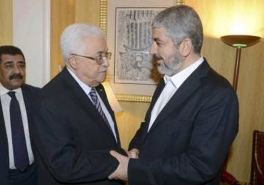 Palestinian President Mahmoud Abbas (L) shakes hands with Hamas chief Khaled Mashaal in Doha May 5,