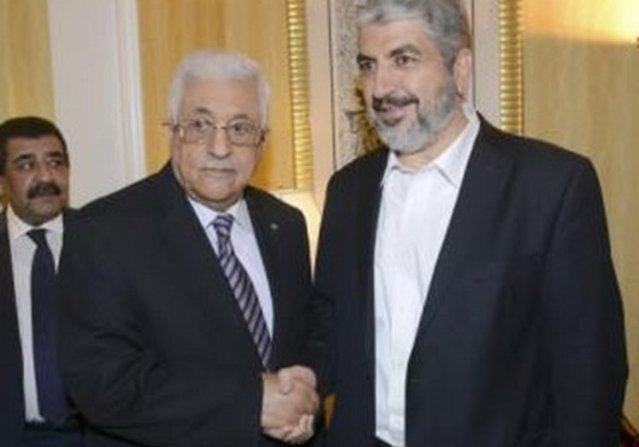 Palestinian President Mahmoud Abbas (L) shakes hands with Hamas chief Khaled Meshaal in Doha May 5,