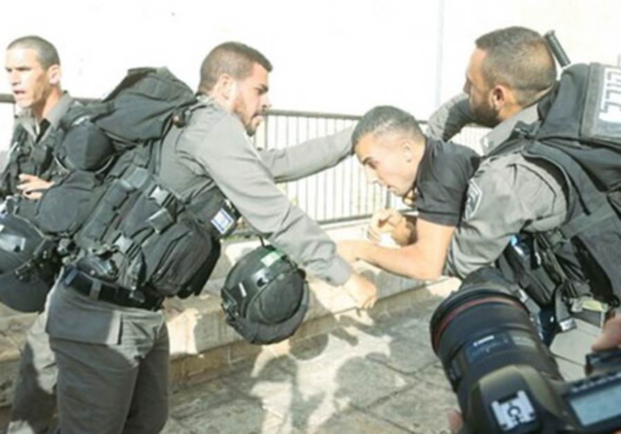 BORDER POLICE detain a Palestinian during clashes at a protest against the Jerusalem Day march, near