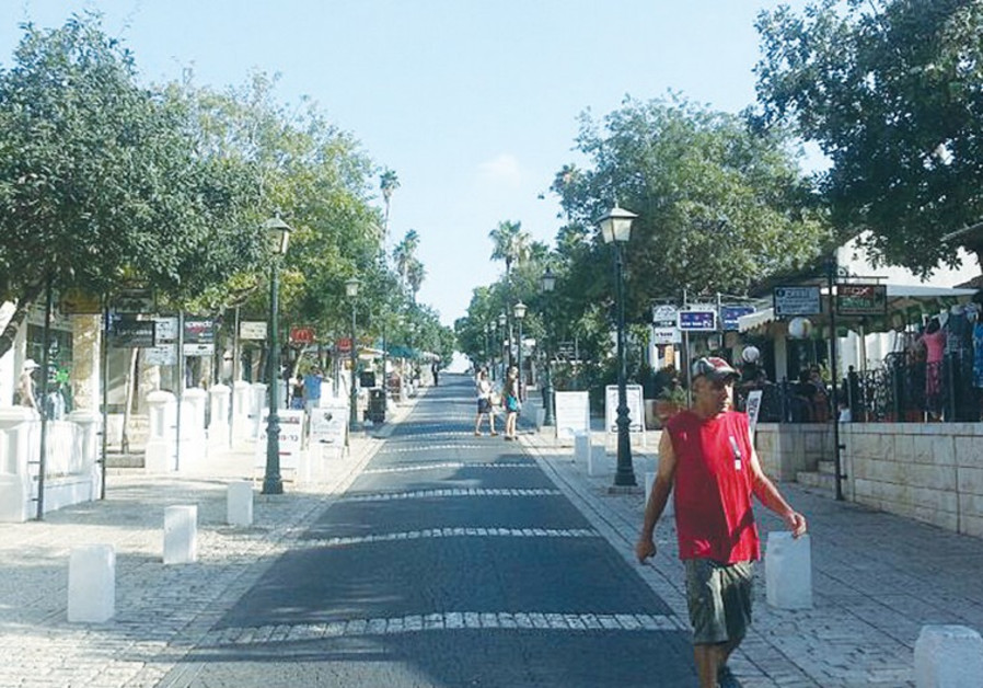 A MAN walks down a street in Zichron Ya'acov yesterday