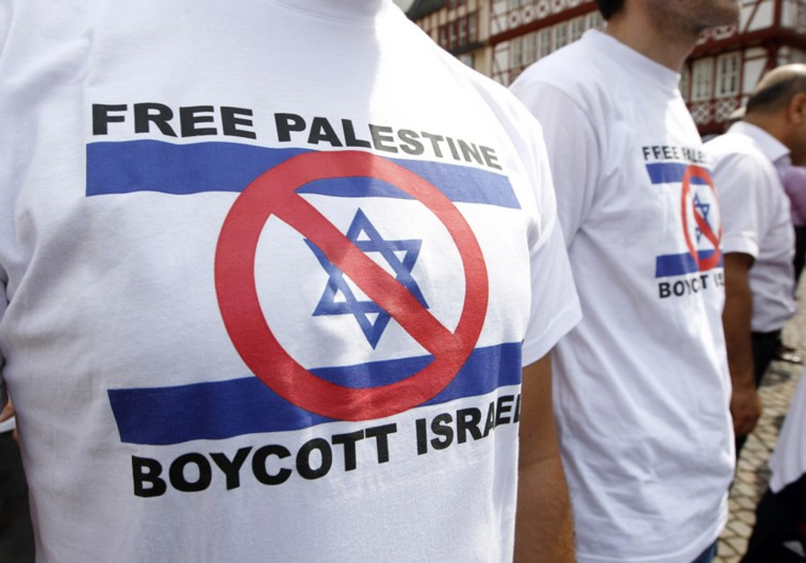 Demonstrators wearing t-shirts depicting a defaced Israeli flag attend a protest against Israel