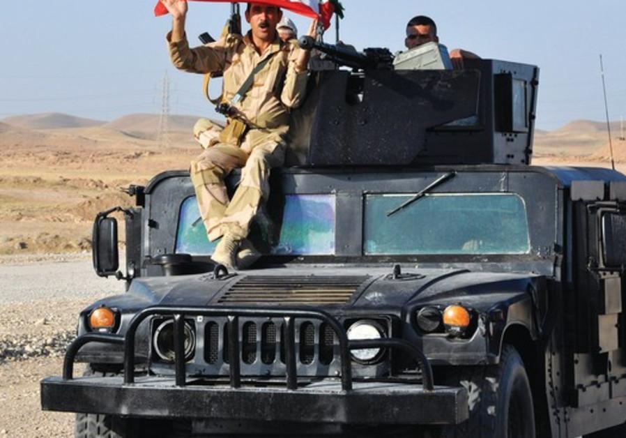 A KURDISH Peshmerga soldier holds a Kurdistan flag.