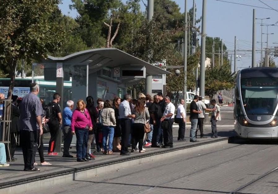 Jerusalem residents waiting at light rail stop at Ammunition Hill, October 23, 2014.