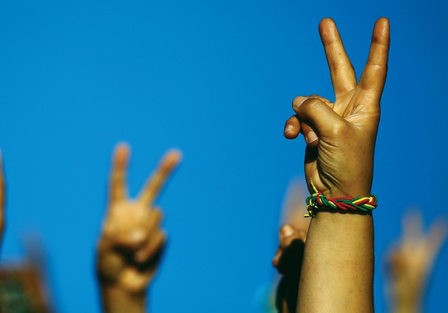 PEOPLE HOLD up peace signs.