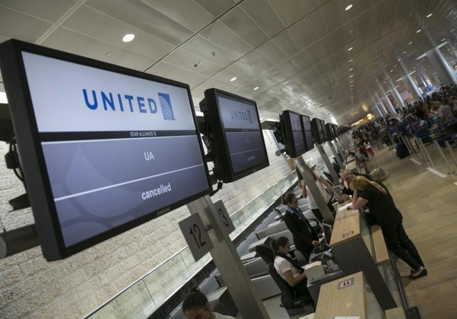 Passengers stand near a check-in desk at Ben-Gurion International Airport, near Tel Aviv