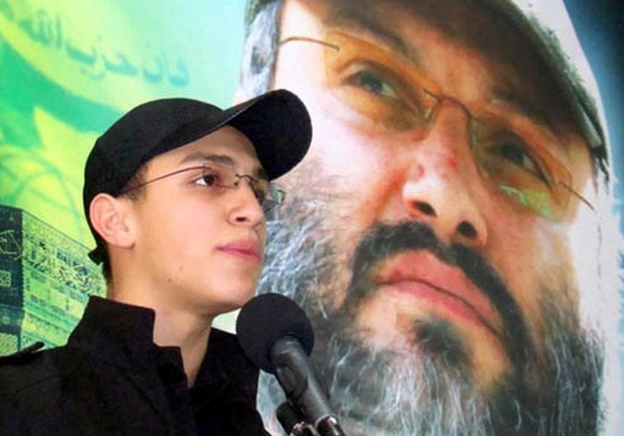Jihad Mughniyeh stands in front of photo of his slain father, Hezbollah commander Imad Mughniyeh