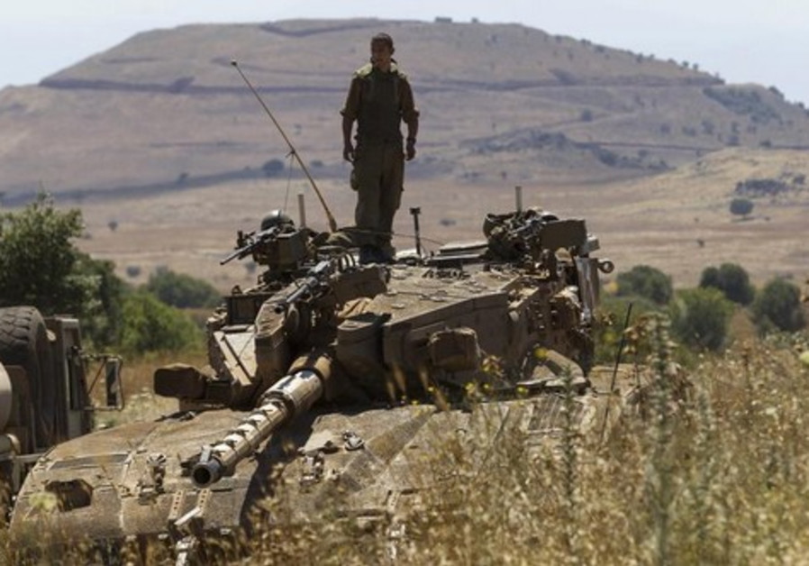 An IDF soldier stands atop a tank near Alonei Habashan on the Golan Heights, close to the ceasefire