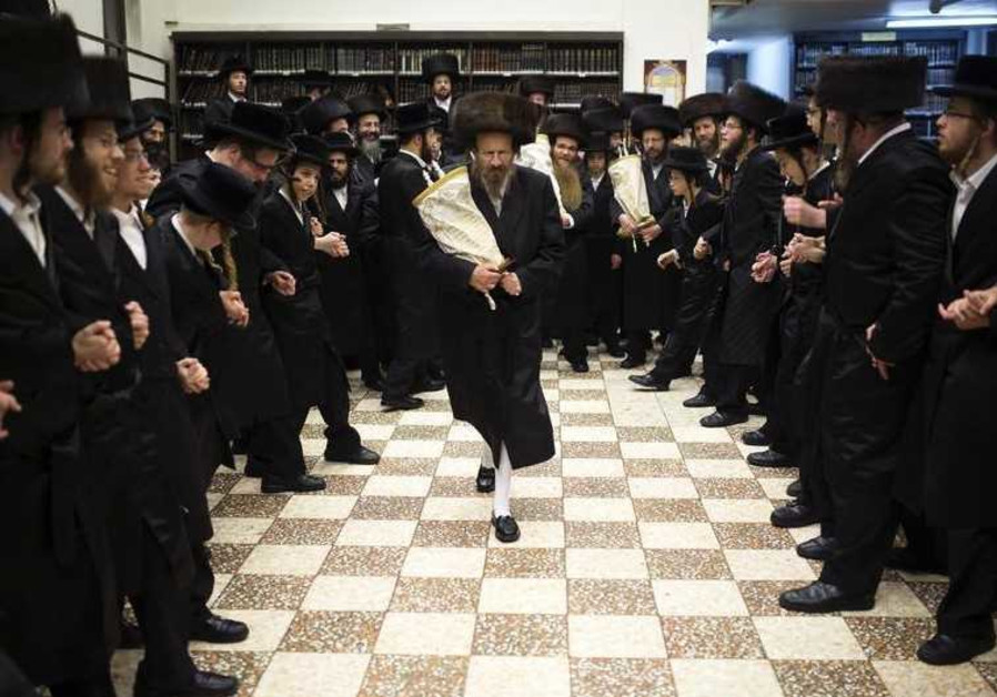 Ultra-Orthodox Jews dance with Torah scrolls during the celebrations of Simchat Torah in a synagogue
