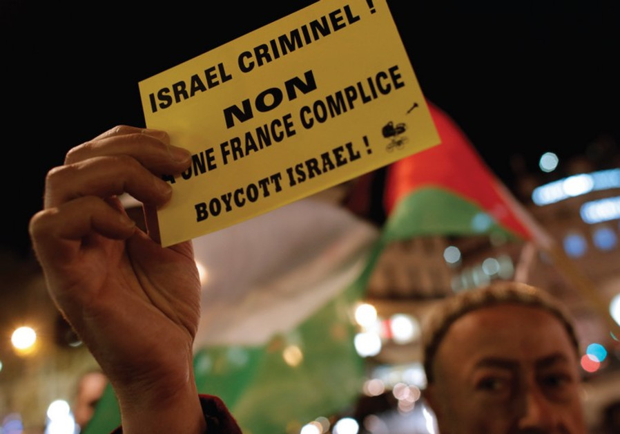 A PALESTINIAN supporter holds a protest leaflet advocating a boycott of Israel in France