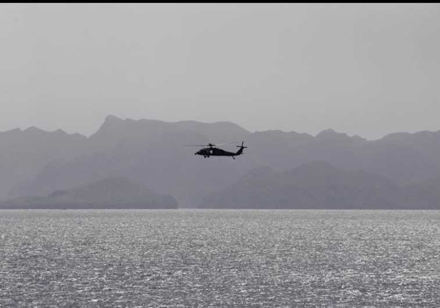 A helicopter patrols the Strait of Hormuz