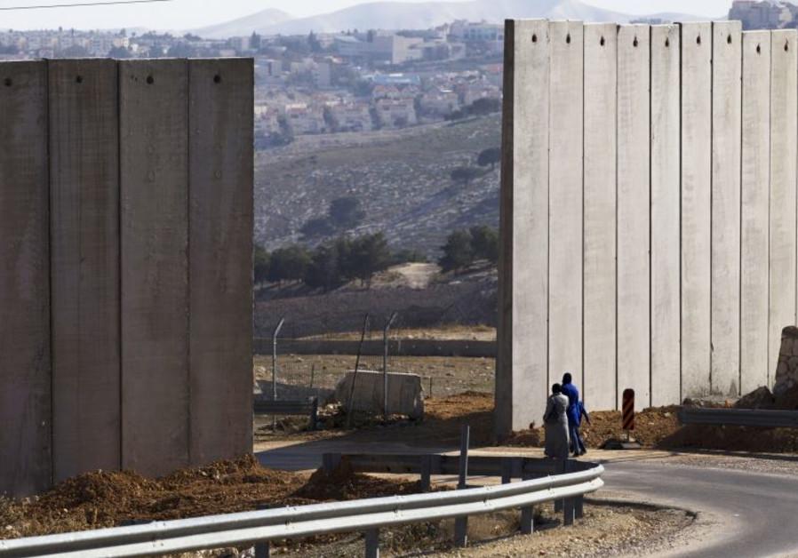 Palestinians walk near an opening in Israel's security fence east Jerusalem