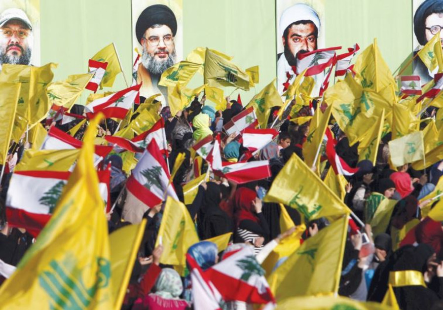 LOCALS IN NABATIYA, south Lebanon, carry Hezbollah and Lebanese flags