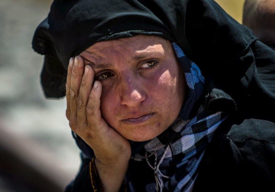 A woman reacts as she rests from walking back to Tel Abyad town, Raqqa governorate
