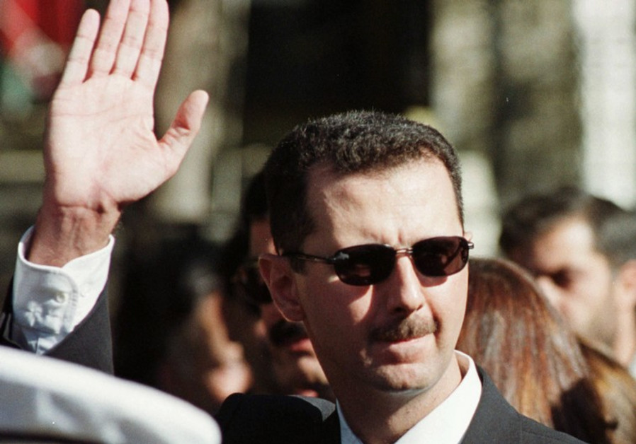 Syrian President Bashar Assad waves to supporters in Damascus