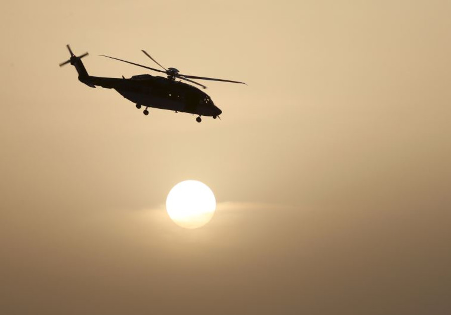 A helicopter of Saudi special forces flies near the setting sun during a graduation ceremony