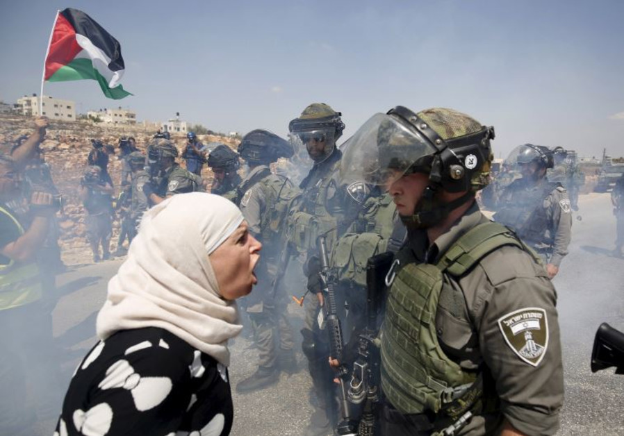 A Palestinian woman argues with an Israeli border policeman during a protest