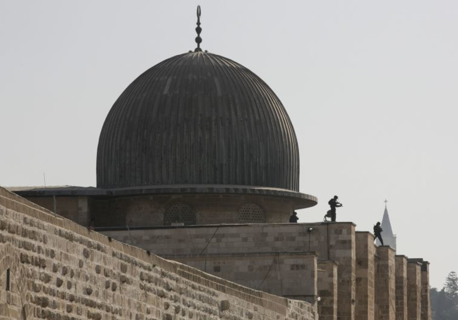 Israeli police officers take positions on the roof of the al-Aksa mosque
