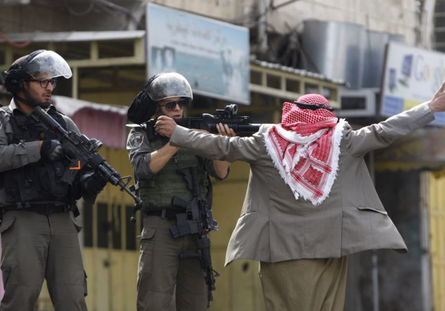 An old Palestinian man prevents Border Policemen from shooting at protesters in Hebron