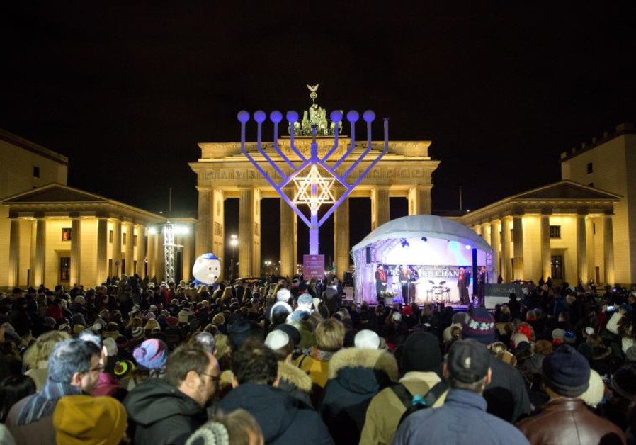 People stand in front of a giant eight- branched candelabrum Menorah in front of the Brandenburg Gat