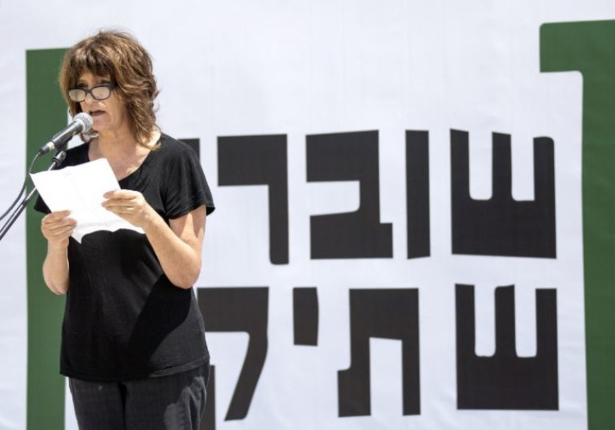A woman reads testimonies during a gathering in Tel Aviv