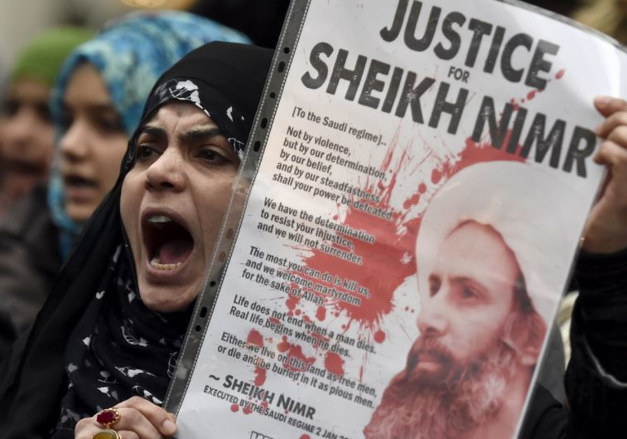A protester holds a placard during a demonstration against the execution of Shi'ite cleric Sheikh Ni