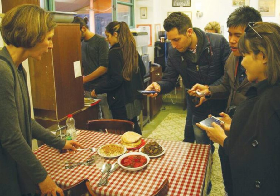 THE VIBE tour participants photograph kubbeh soup in Jerusalem's Mahaneh Yehuda market on Friday.