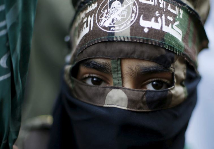 A masked Palestinian boy wearing the headband of Hamas's armed wing