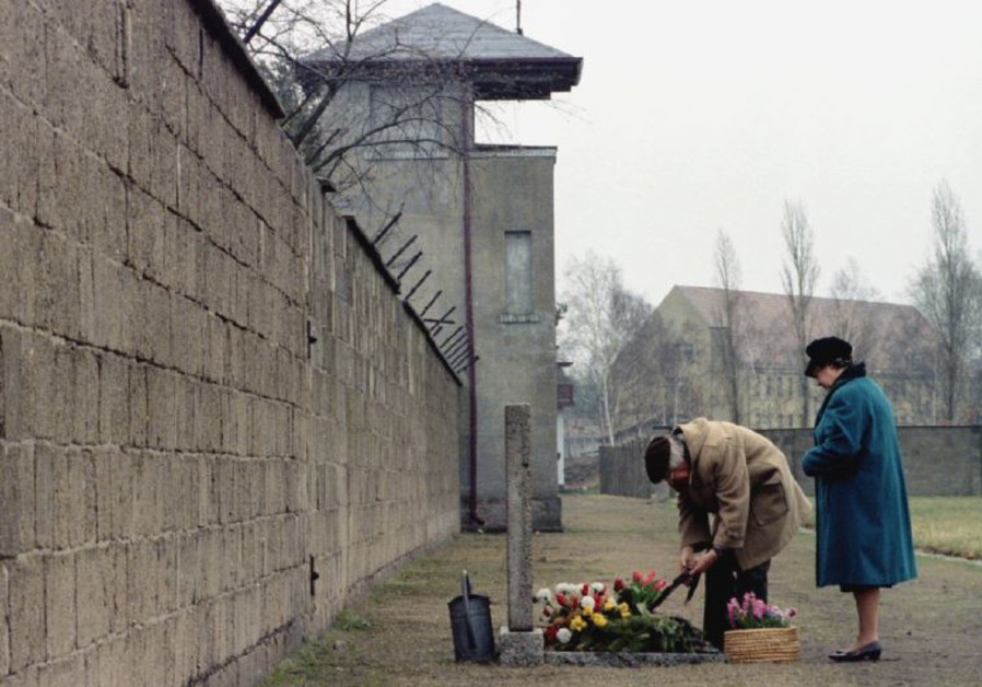 An elderly couple lays a wreath in front of a memorial for the victims of Sachsenhausen