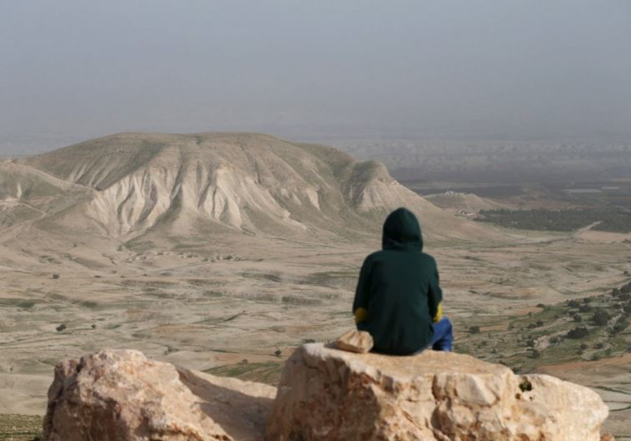 A Palestinian man sits on a rock at Jordan Valley near the West Bank city of Jericho