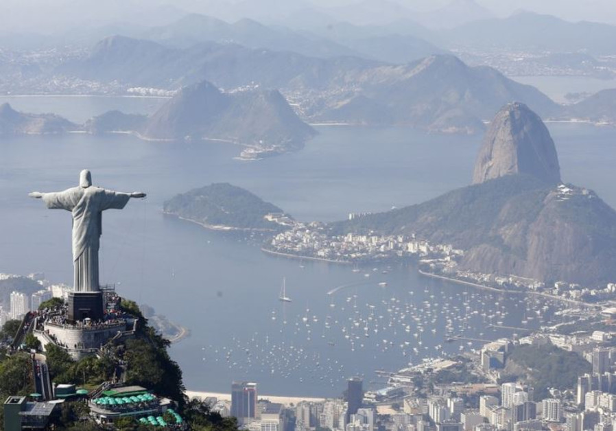Tourists visit the Christ the Redeemer statue with Sugarloaf Mountain (R) in Rio de Janeiro