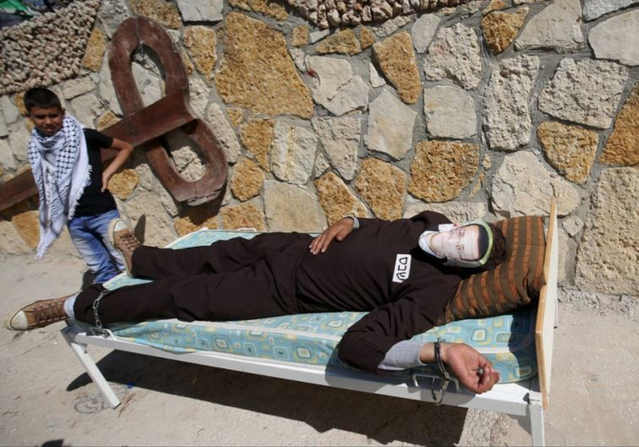 A Palestinian lies on a bed to protest detention of a hunger-striking prisoner