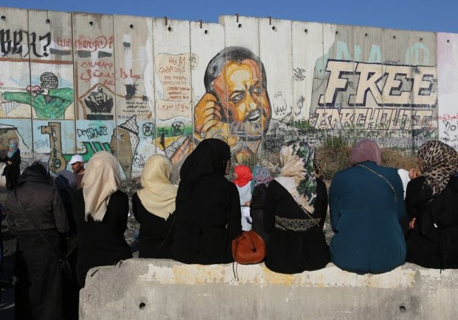 Palestinian women sit near a section of Israel's separation barrier at Qalandia checkpoint
