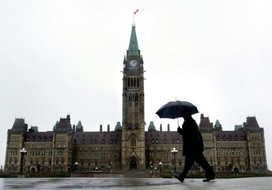 A pedestrian walks in the rain on Parliament Hill in Ottawa, Canada.