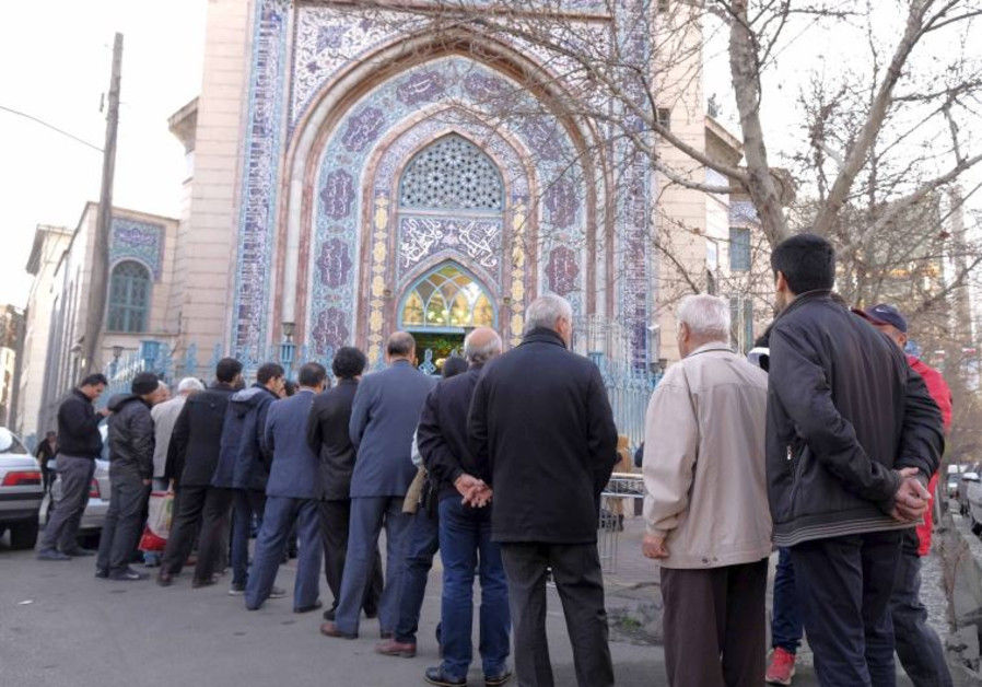 Iranians stand in line to cast their votes during elections for the parliament