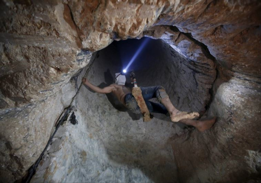 A Palestinian worker is lowered on a rope into a smuggling tunnel that was flooded by Egypt