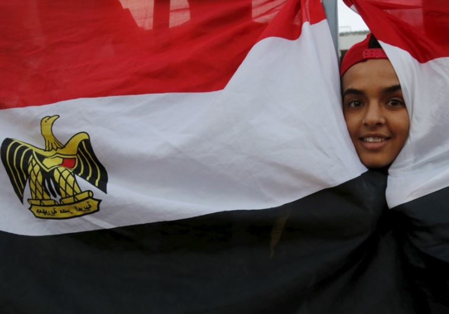 An Egyptian fan cheers behind the national flag before a 2018 World Cup qualifying soccer match