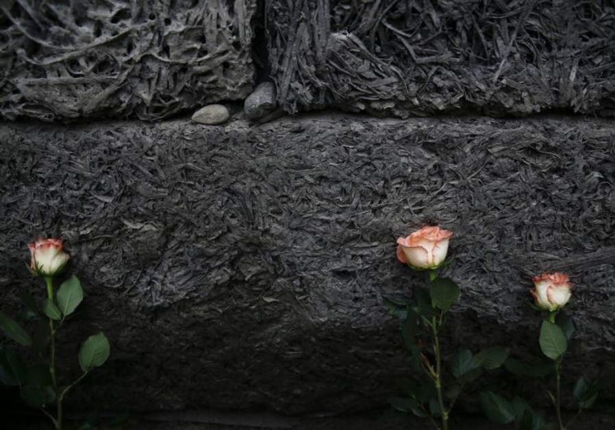 """Flowers are placed at the """"death wall"""" at Auschwitz"""