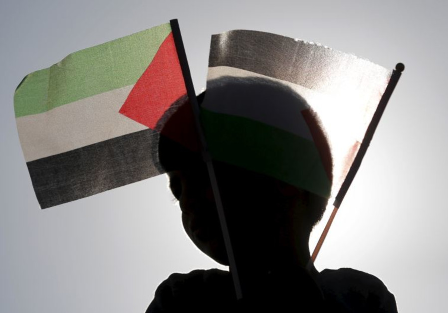 A Beduin boy holds Palestinian flags as he takes part in a rally marking Land Day in Umm el-Hiran