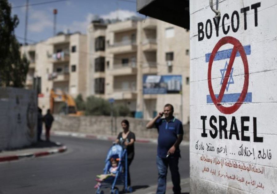Palestinians walk past a sign calling for a boycott of Israel painted on a wall in Bethlehem