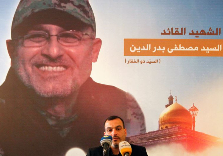 A man reads the Koran in front of a picture depicting top Hezbollah commander Mustafa Badreddine