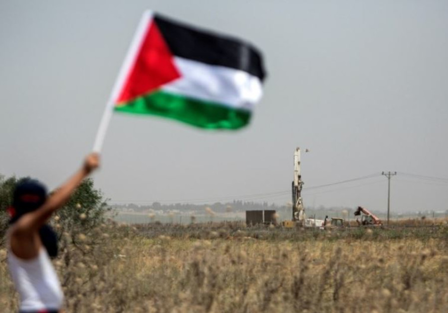 A Palestinian youth waves the national flag as the IDF digs in search of smuggling tunnels